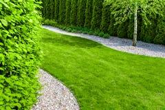 Jardin formel avec un chemin de petites pierres, de bordure de haies et de pelouse verte Photos stock