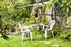 Jardin luxuriant de cottage d'été avec des meubles de patio Photographie stock