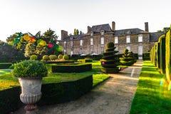 Jardin régulier dans peu de château français, temps de coucher du soleil photo stock