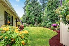 Jardin soigné à l'arrière-cour avec des arbres, des buissons et des fleurs photographie stock libre de droits