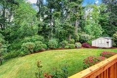 Jardin soigné à l'arrière-cour avec des arbres, des buissons et des fleurs images stock