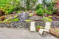Jardin soigné avec des roches desing Secteur concret de patio de plancher avec deux chaises image stock