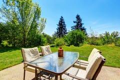 Jardin soigné d'arrière-cour avec des arbres et des buissons Vue d'ensemble de table de patio photographie stock libre de droits