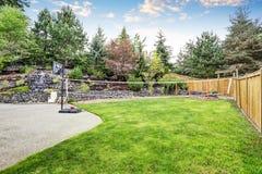 Jardin soigné d'arrière-cour avec les roches desing, le cercle de basket-ball et le filet de volleyball photographie stock