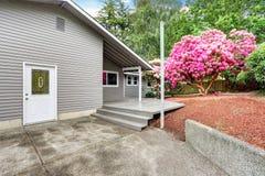 Jardin soigné d'arrière-cour de maison d'équilibre de voie de garage avec la plate-forme en bois de débrayage photo stock