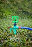 Jardinage Arroseuse automatique de pelouse sur l'herbe verte extérieur Images libres de droits