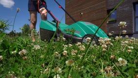 Jardinage travaillant de jeune femme équilibrant l'herbe avec la tondeuse à gazon Tir de cardan banque de vidéos