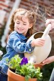 Jardinagem: Estações de tratamento de água de ajuda da menina do pai Imagens de Stock