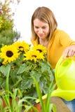 Jardinagem - flores de derramamento da mulher imagem de stock royalty free
