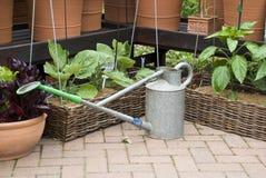 Jardinagem - lata molhando e potenciômetros de flor Foto de Stock Royalty Free