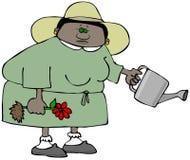 Jardineiro étnico da mulher que guarda uma flor e uma lata molhando Foto de Stock Royalty Free