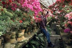 Jardineiro bonito da jovem mulher com as tran?as e a faixa vermelha que descansam ap?s o trabalho duro com as flores da mola na e imagens de stock