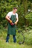 Jardineiro com ajustador do gramado fotografia de stock