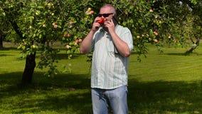 Jardineiro com maçã e telefone esperto no pomar de maçã video estoque