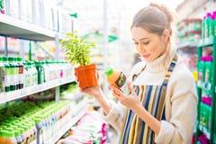 Jardineiro da mulher que lê sobre produtos químicos agrícolas para flores e plantas Imagem de Stock Royalty Free