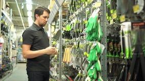 Jardineiro do homem na loja do hardware que escolhe a pá pequena do jardineiro vídeos de arquivo