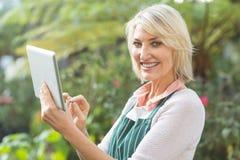 Jardineiro fêmea maduro feliz que usa a tabuleta digital fotos de stock
