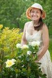 Jardineiro fêmea na planta cor-de-rosa foto de stock