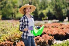 Jardineiro fêmea novo que molha as plantas no jardim imagens de stock