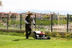 Jardineiro latino-americano Mowing With uma opinião da cume Foto de Stock Royalty Free