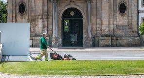 Jardineiro municipais que segam a grama no centro da cidade Imagem de Stock Royalty Free