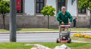 Jardineiro municipais que segam a grama no centro da cidade Fotografia de Stock