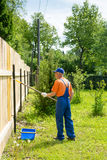 Jardineiro na cerca de madeira nova das pinturas uniformes azuis Foto de Stock Royalty Free