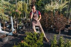 Jardineiro novo que fala no smartphone ao descansar durante o trabalho no jardim fotografia de stock royalty free