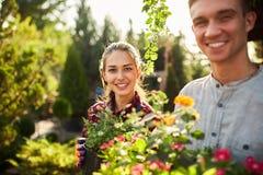 Jardineiro potenci?metros felizes da posse do menino e da menina com as plantas em jardins bonitos em um dia ensolarado morno fotos de stock