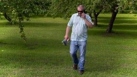 Jardineiro que anda e que fala no telefone no pomar de maçã video estoque