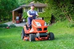 Jardineiro que conduz um cortador de grama da equitação no jardim fotos de stock royalty free