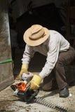 Jardineiro que usa o tanque de gasolina de enchimento da ferramenta elétrica Fotografia de Stock