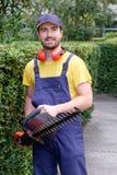 Jardineiro que usa uma tosquiadeira da conversão no jardim Fotografia de Stock