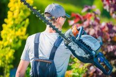 Jardinero con el condensador de ajuste de seto fotografía de archivo libre de regalías