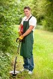 Jardinero con el condensador de ajuste del césped imagenes de archivo