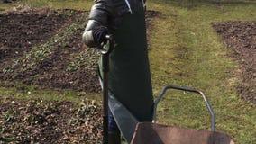 Jardinero de la mujer con dolor de espalda cerca de la bifurcación y de la carretilla almacen de video