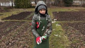 Jardinero de la mujer con las ramas del sauce y las tijeras de la poda que camina en jardín almacen de metraje de vídeo