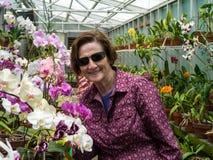 Jardinero de más viejas mujeres con las orquídeas Imagen de archivo