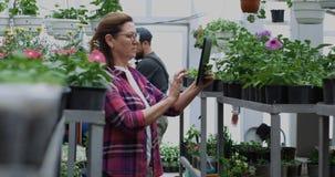 Jardinero de sexo femenino que toma la foto en invernadero