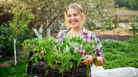 Jardinero de sexo femenino de risa feliz que presenta con los almácigos del tomate en el jardín Imagen de archivo libre de regalías