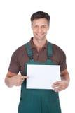 Jardinero de sexo masculino que lleva a cabo el cartel en blanco Fotos de archivo libres de regalías