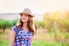 Jardinero en la camisa y el sombrero comprobados, naturaleza soleada verde Imagen de archivo libre de regalías