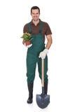 Jardinero joven feliz que sostiene las flores Fotos de archivo libres de regalías