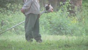 Jardinero Mows la hierba verde del cortacésped metrajes