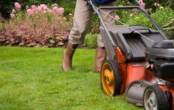 Jardinero que siega el césped. Foto de archivo