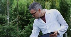 Jardinero que usa la tableta en jardín del cuarto de niños almacen de metraje de vídeo