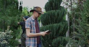 Jardinero que usa la tableta en jard?n del cuarto de ni?os almacen de video