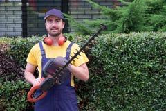 Jardinero que usa podadoras del seto foto de archivo libre de regalías