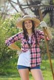 Jardinero sonriente hermoso con un rastrillo Foto de archivo