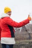 Jardinero sonriente joven de la mujer en un sombrero y una chaqueta con el pulgar para arriba Fotos de archivo
